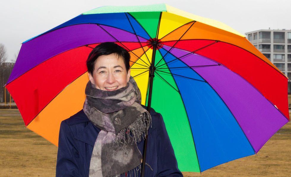Hanna Holopainen ja iso sadevarjo sateenkaaren väreissä